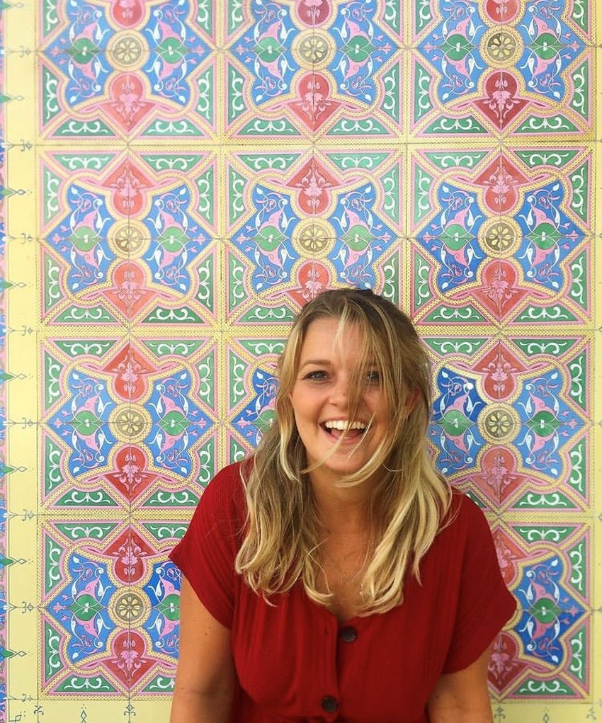 Alice Coventry, Lumos employee, in front of a tiled wall