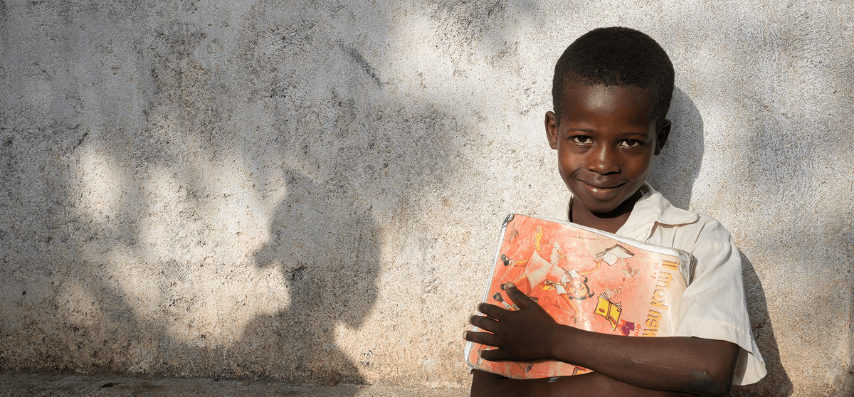 Diego, from Haiti, stands against a wall outside his school