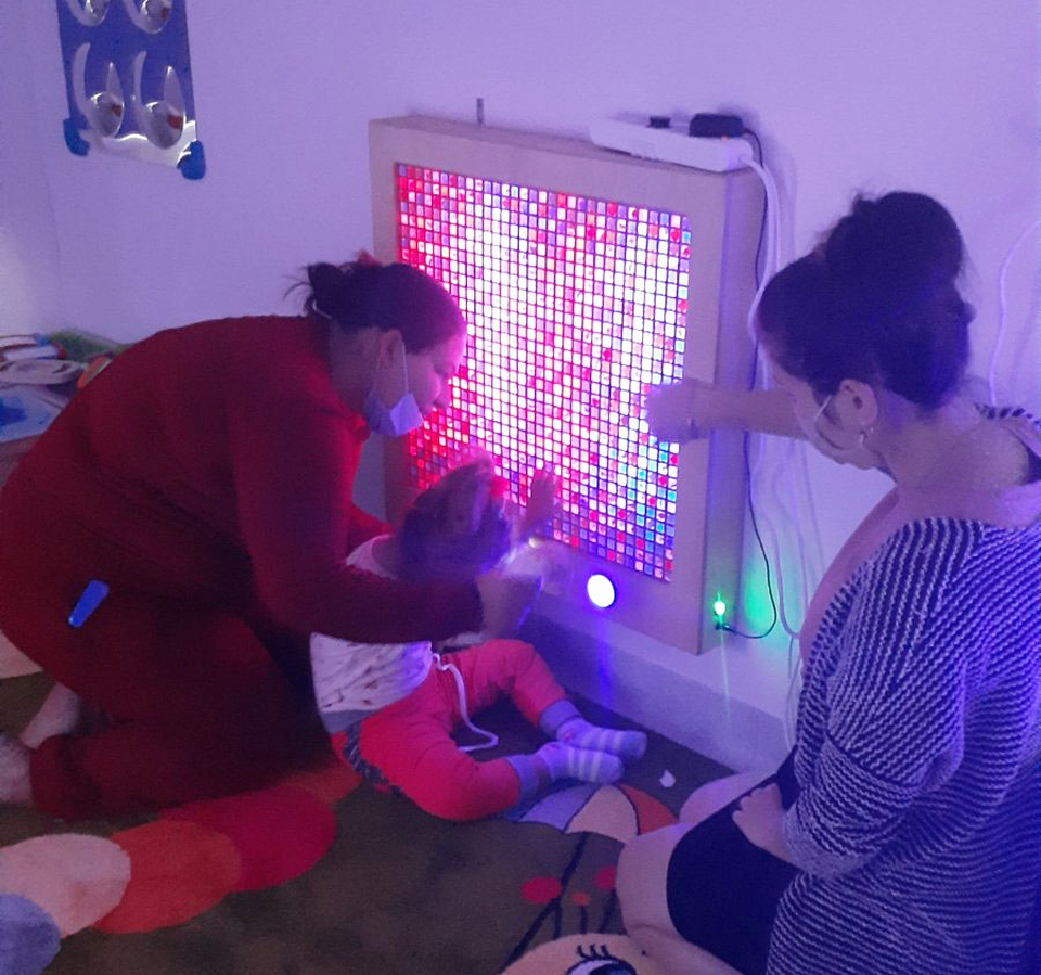 A young person takes part in a light sensory therapy session at the centre.