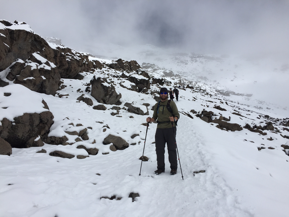 Bryan standing on a snow covered mountain, mid-way through his climb