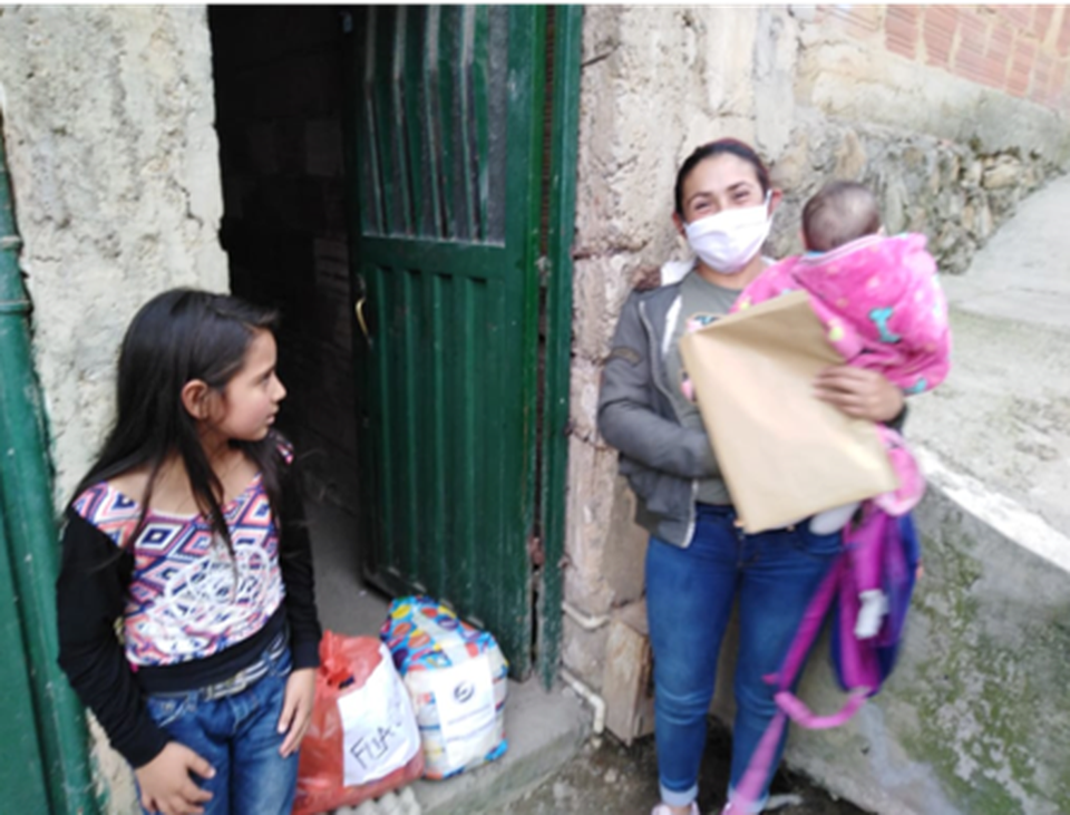 Maria and her children outside their home in Bogotá