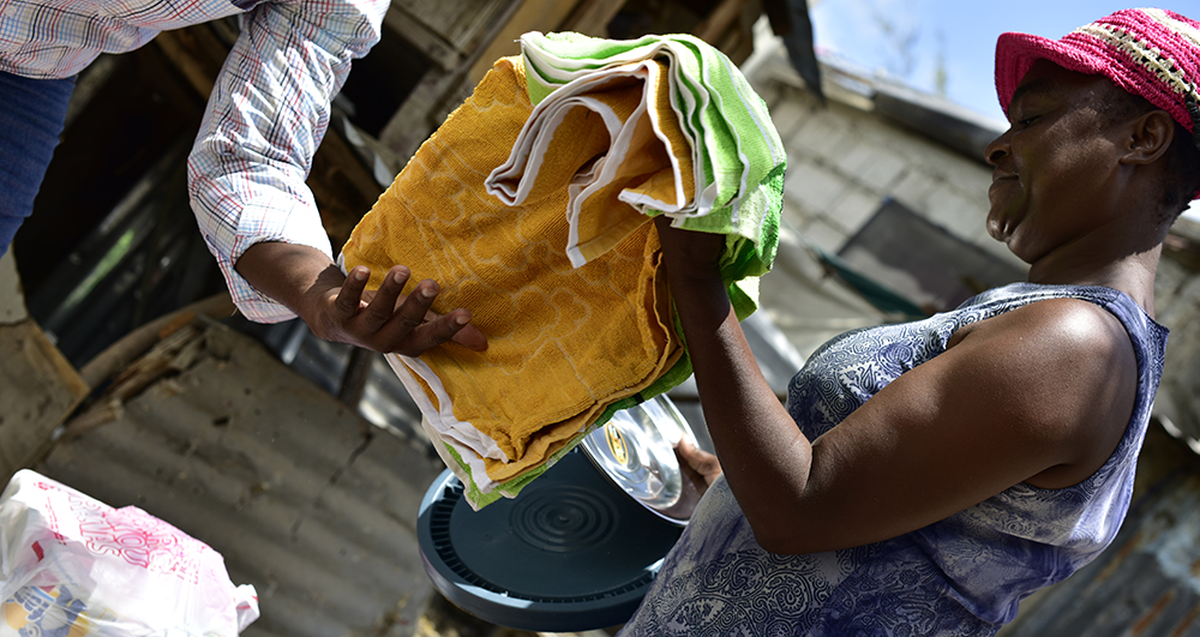 One of the team in Haiti wearing a blue top and a hat sorting through some items for hygiene kits