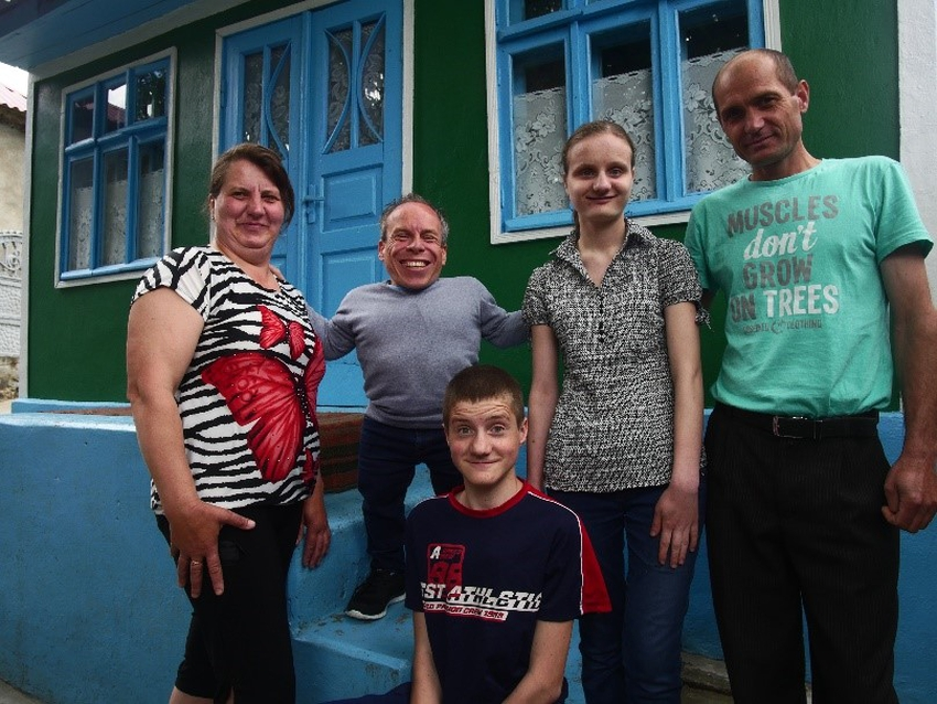 Warwick Davis with a family in Moldova